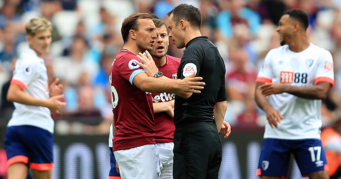 LONDON, ENGLAND - AUGUST 18: Mark Noble and Jack Wilshere of West Ham United speak with Match Referee, Stuart Attwell during the Premier League match between West Ham United and AFC Bournemouth at London Stadium on August 18, 2018 in London, United Kingdom. (Photo by Marc Atkins/Getty Images)