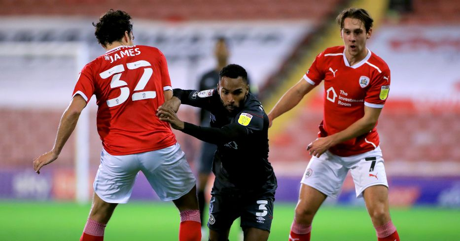 Rico Henry battles for the ball with Matty James and Callum Brittain