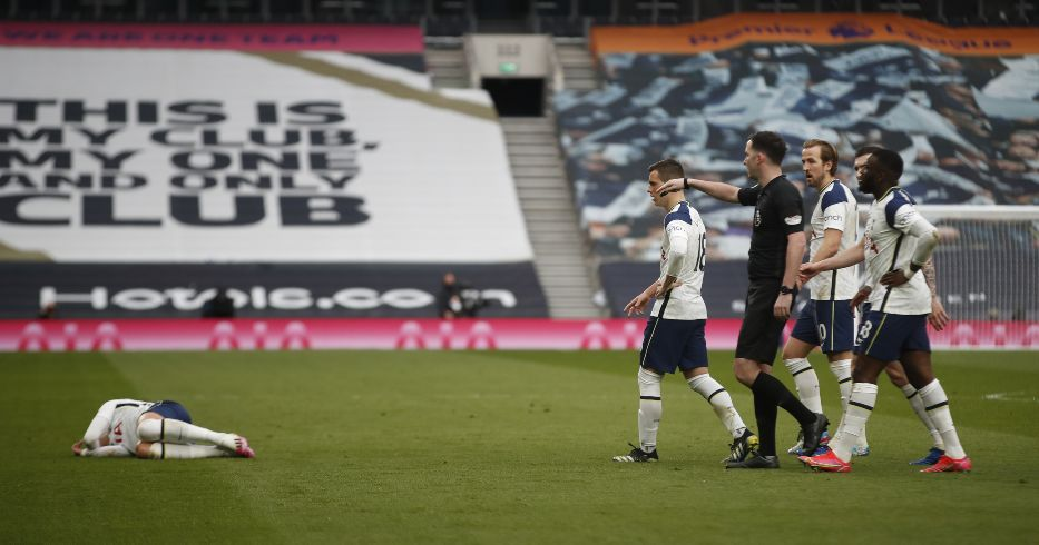 Chris Kavanagh is surrounded by Tottenham players