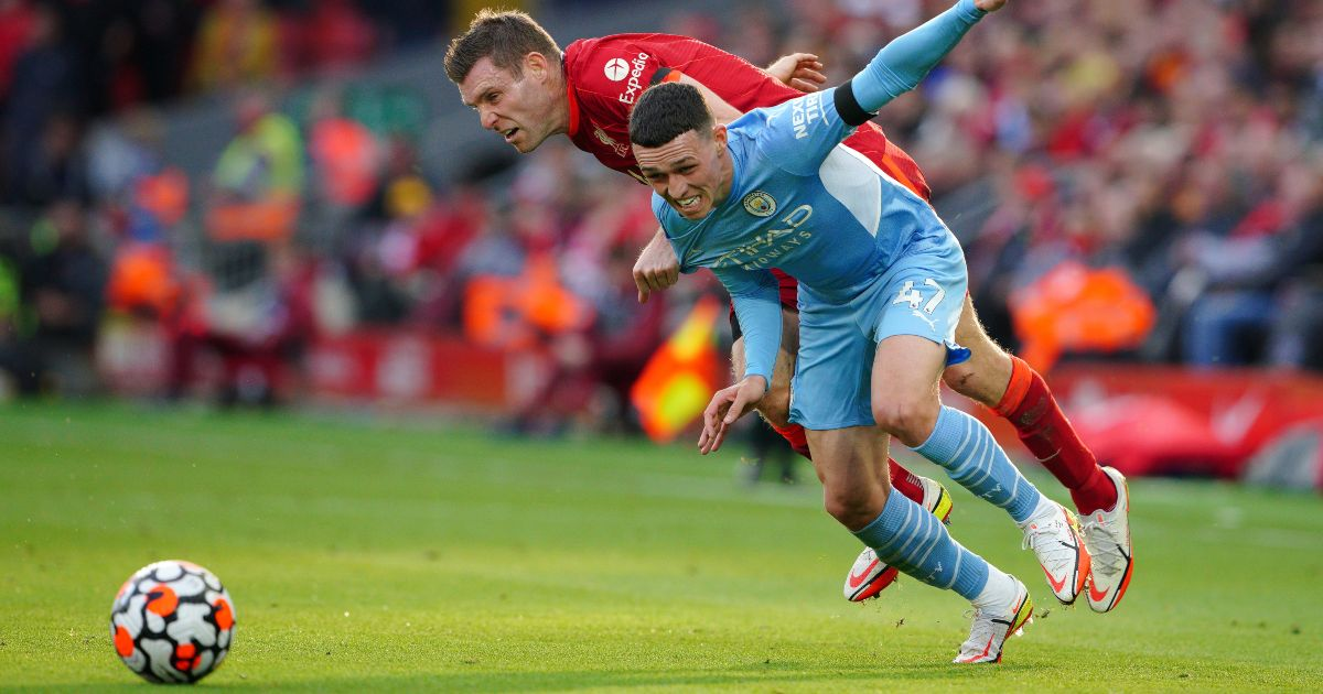 Phil Foden beats Liverpool defender James Milner to the ball
