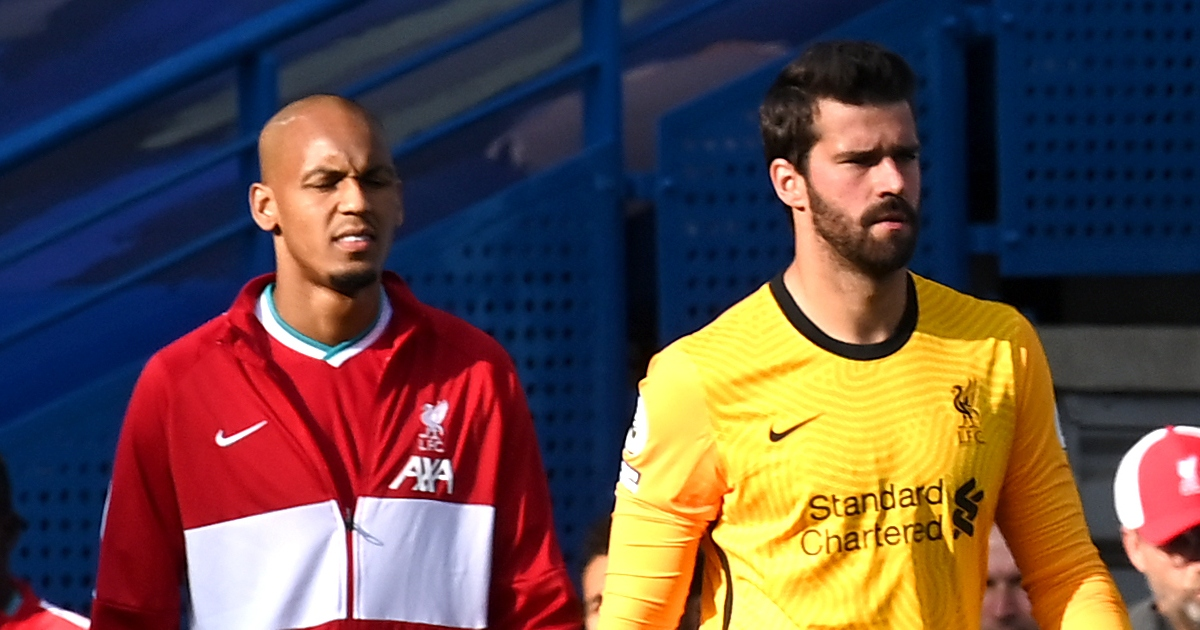 Liverpool's Fabinho and Alisson walk out onto the pitch